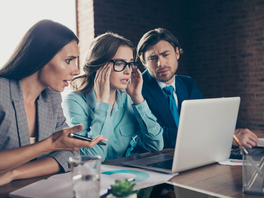 confused business team looking at laptop