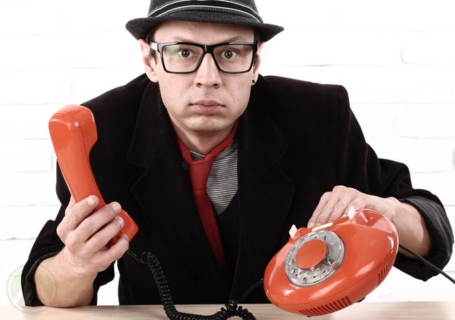 perplexed man holding landline telephone