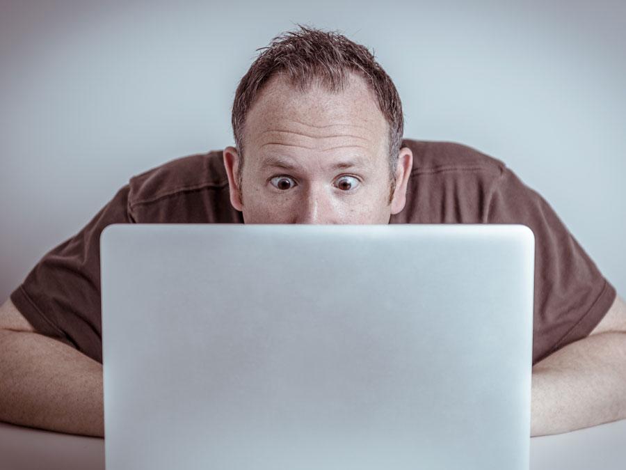 surprised man staring at laptop