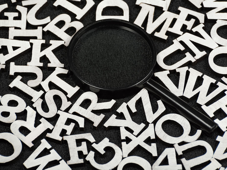 white letters around black magnifying lens