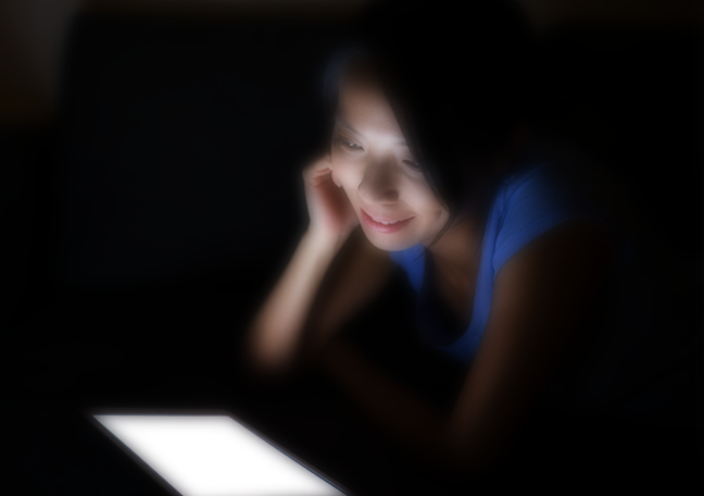 woman reading tablet in the dark