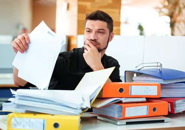 young office employee with folders of document studying printed report