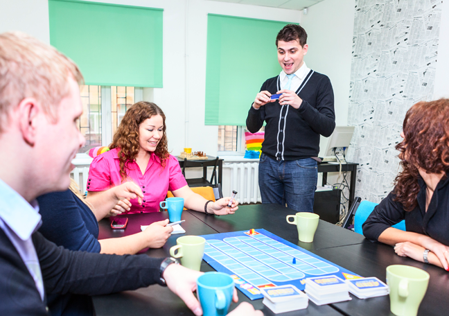 young people having fun playing board games