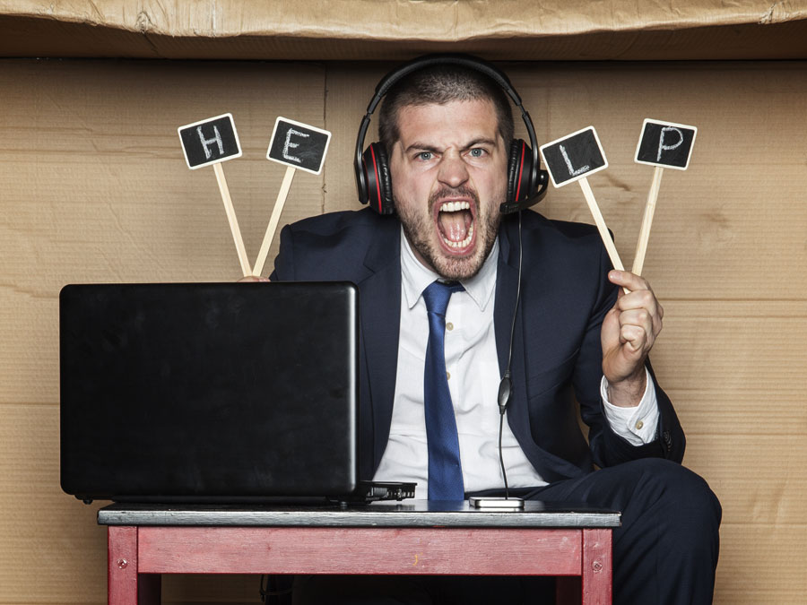 angry call center agent working in cardboard box holding help sign