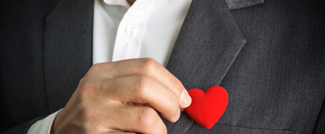 businessman holding stuffed heart close to chest