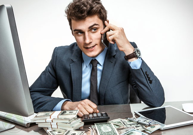 businessman with piles of money making phone call
