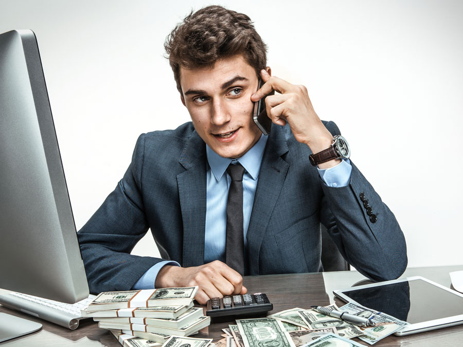 confident businessman on the phone at his office table with computer money calculator
