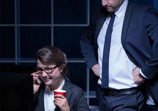 employee in phone call displeased boss behind