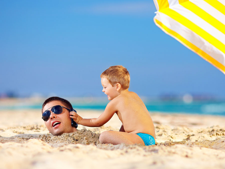 father and son in beach using phone under yellow umbrella