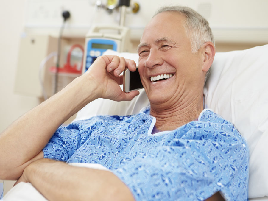 senior gentleman in hospital bed using smartphone