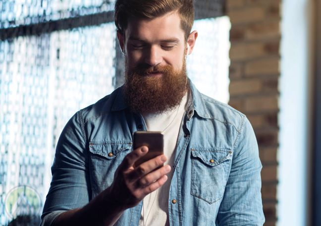 smiling bearded man reading smartphone