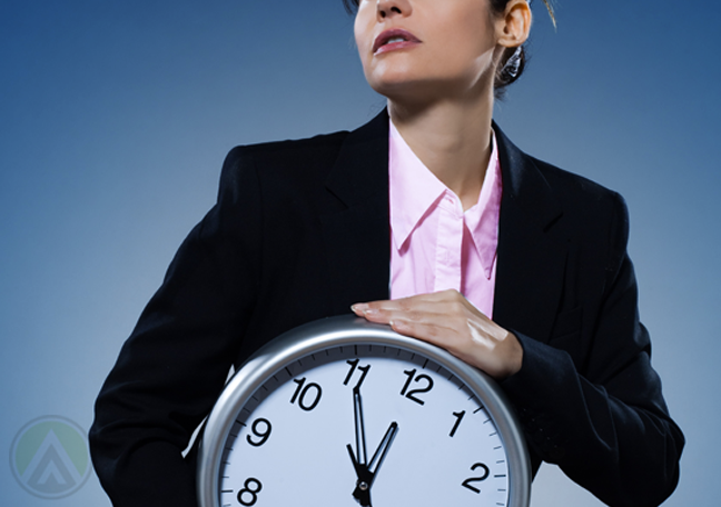 business executive holding wall clock to chest