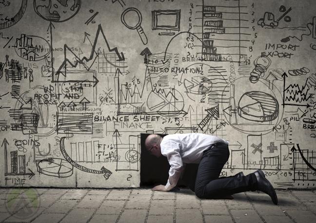 businessman kneeling opening hole in wall