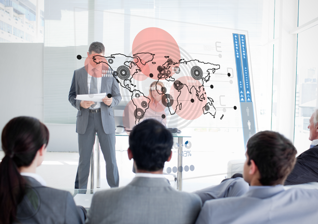 businessman looking at reports in presentation with executives watching