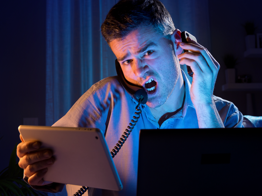 busy man at home using tablet laptop on the phone with customer service agent