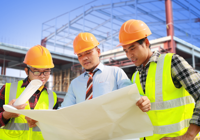 engineers at construction site looking floor plans