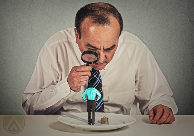 middle aged businessman looking through magnifying glass at tiny man on dinner plate