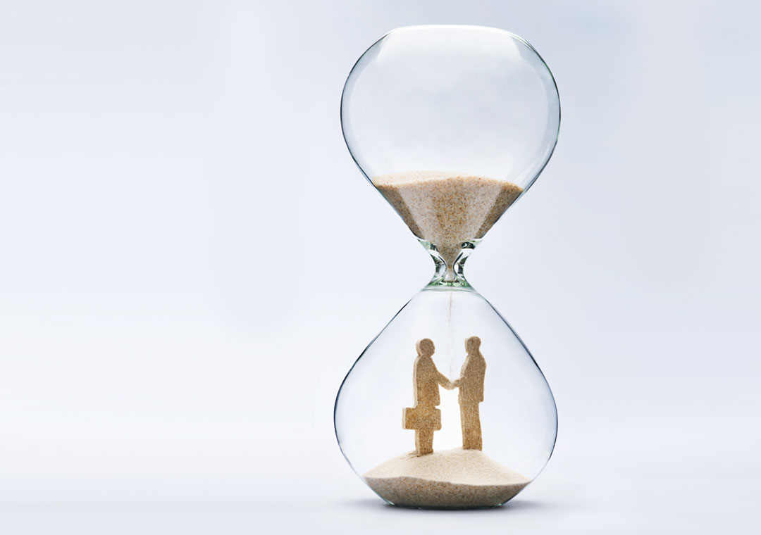 miniature business executives making business plans partnership shaking hands in hourglass