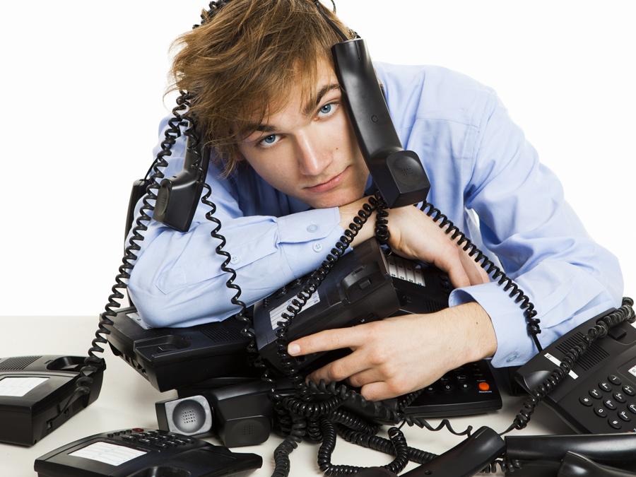 sad businessman on entangled telephones