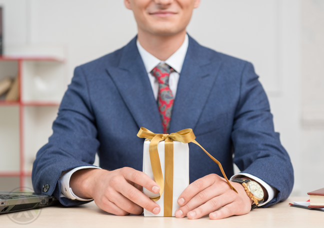 smiling employee with wrapped gift
