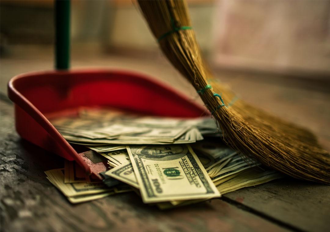 sweeping money into dustpan