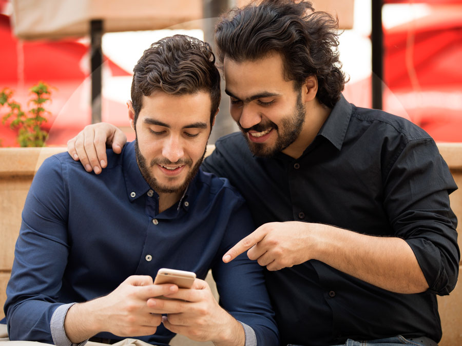 Arabic friends talking about smartphone use