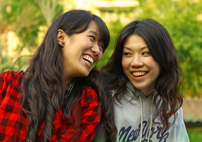 asian best friends smiling looking at each other