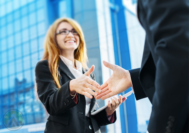 business executive shaking hands with business partners outside building