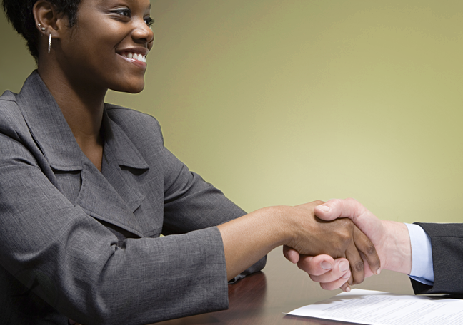 female employee shaking hands with company boss off-panel