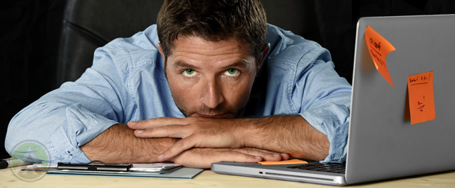 frustrated employee sitting by laptop