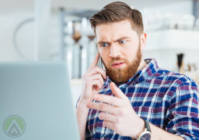 frustrated office employee on the phone pointing to laptop