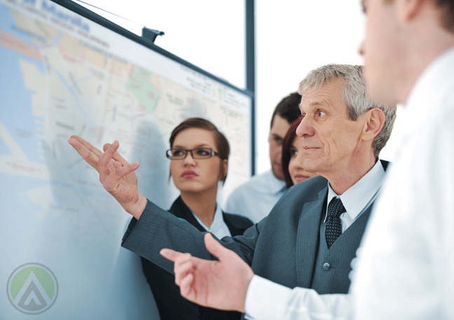 middle aged businessman pointing to map flanked by younger business team