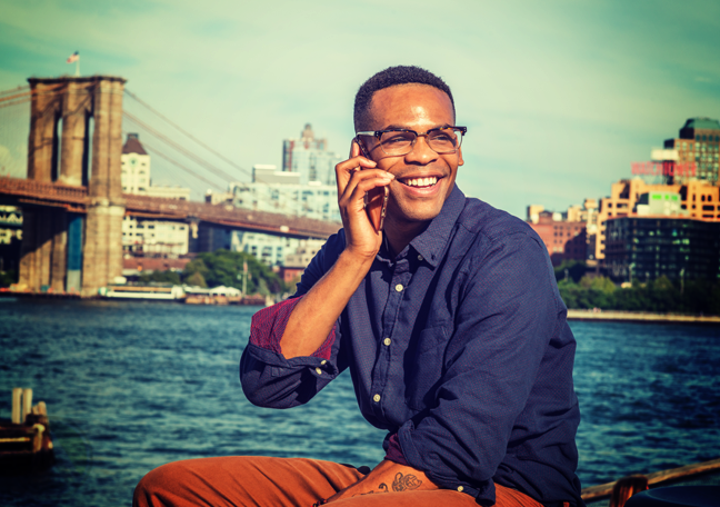 smiling man in phone call by river by cityscape