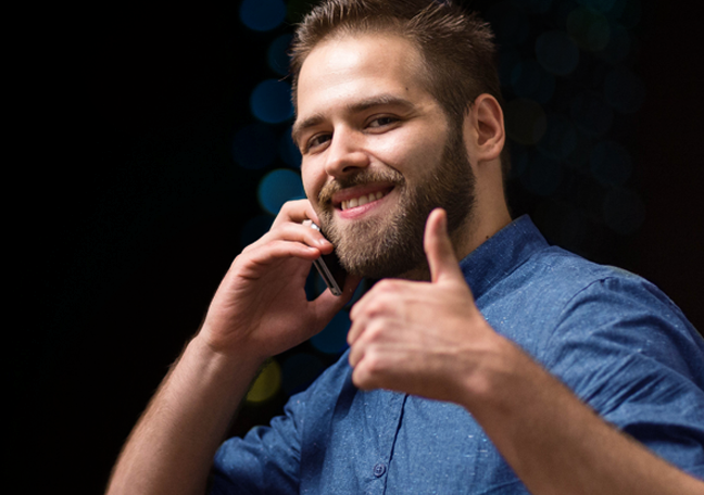 smiling man on phone giving thumbs up