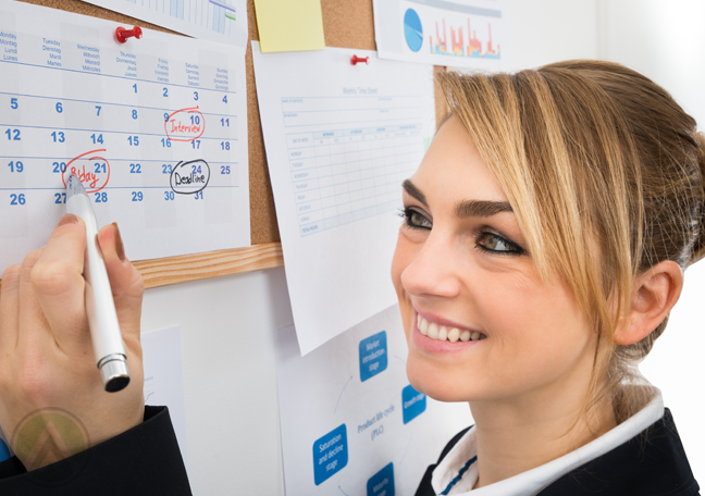 smiling office employee crossing out days on calendar