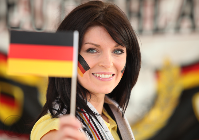 woman smiling brightly holding up german flag