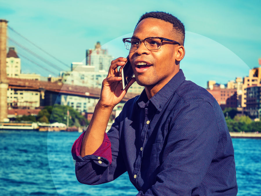 young african american man in glasses speaking on phone in seaside