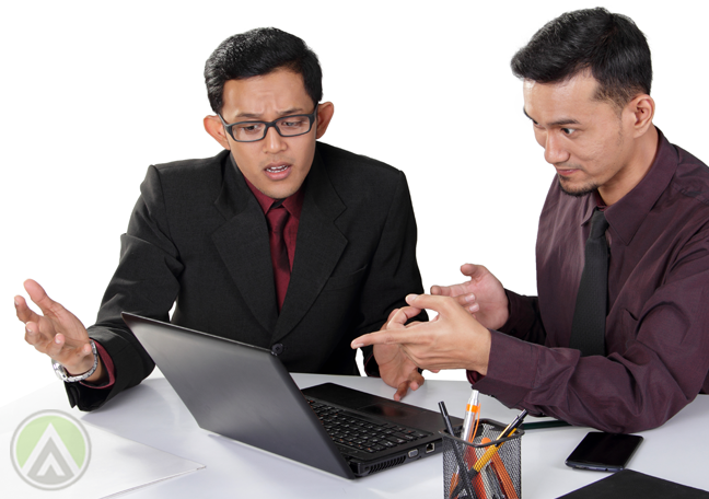 Asian coworkers discussing work on laptop