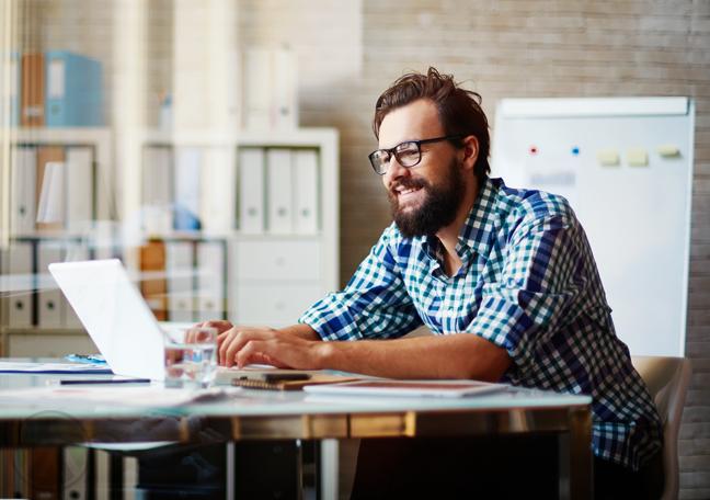 bearded man using laptop in office lounge