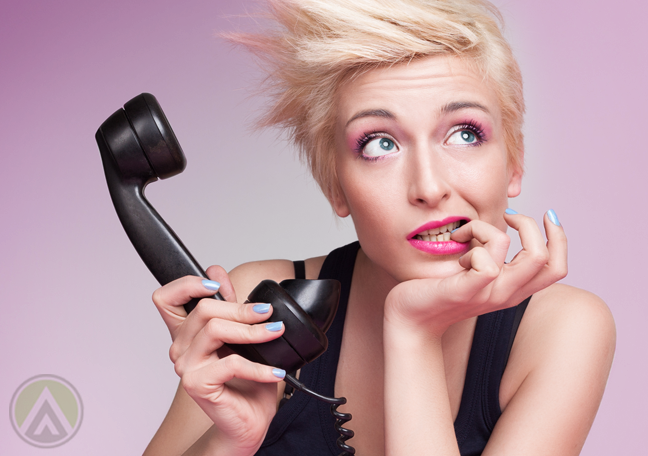 blonde pixie girl biting finger holding landline phone