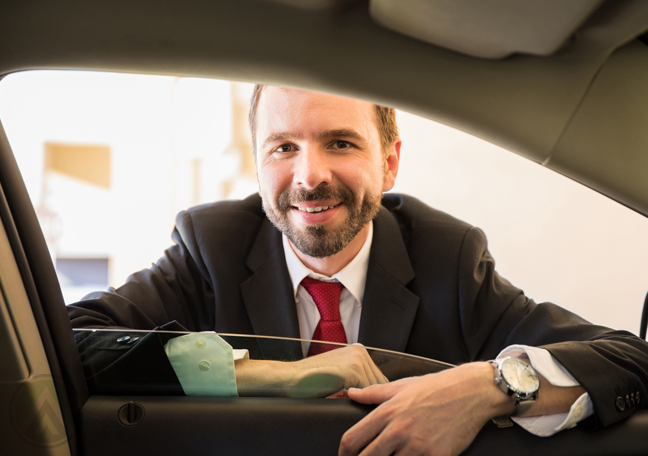 businessman smiling from outside car door
