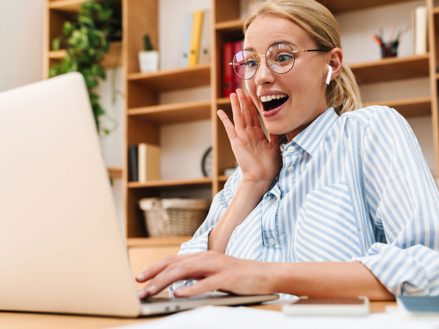 delighted woman in glasses using laptop