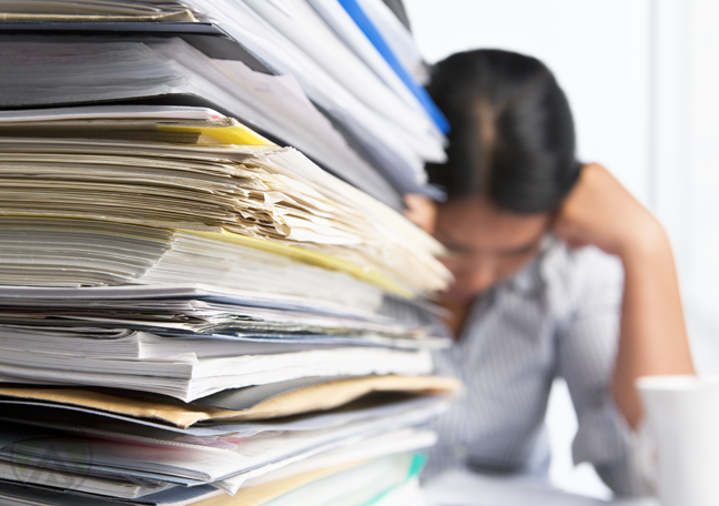 employee reading behind large pile of printed paperwork research reports