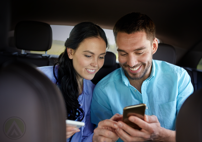 happy couple using smartphone in back of car