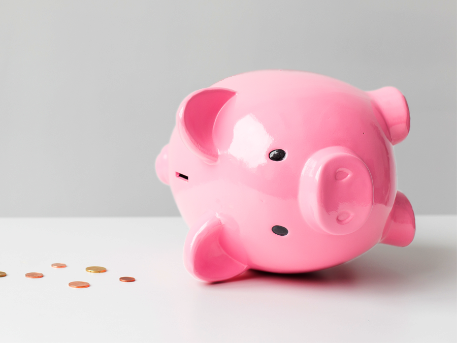 piggybank on its side with coins spilling out