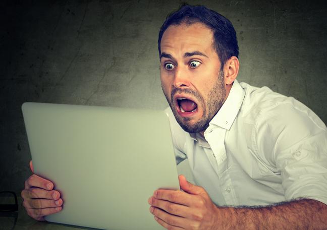 screaming businessman panicking over laptop