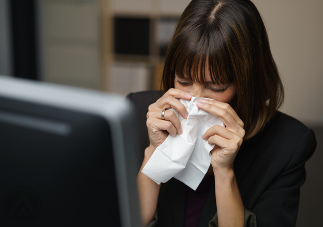 sick office employee blowing nose on tissue