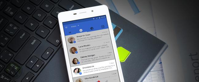 smartphone showing facebook inbox on top of laptop keyboard