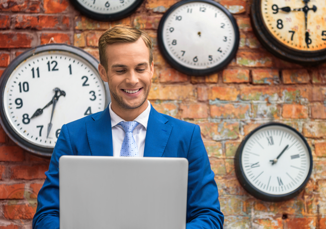 smiling businessman in blue suit by red brick wall with wall clocks