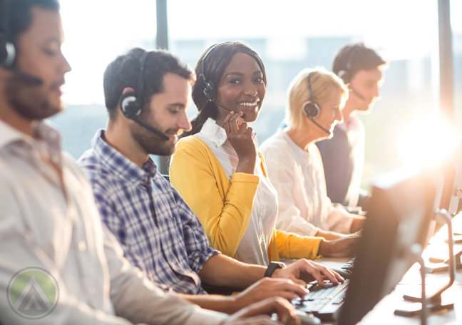 smiling call center agent surrounded by busy customer service coworkers
